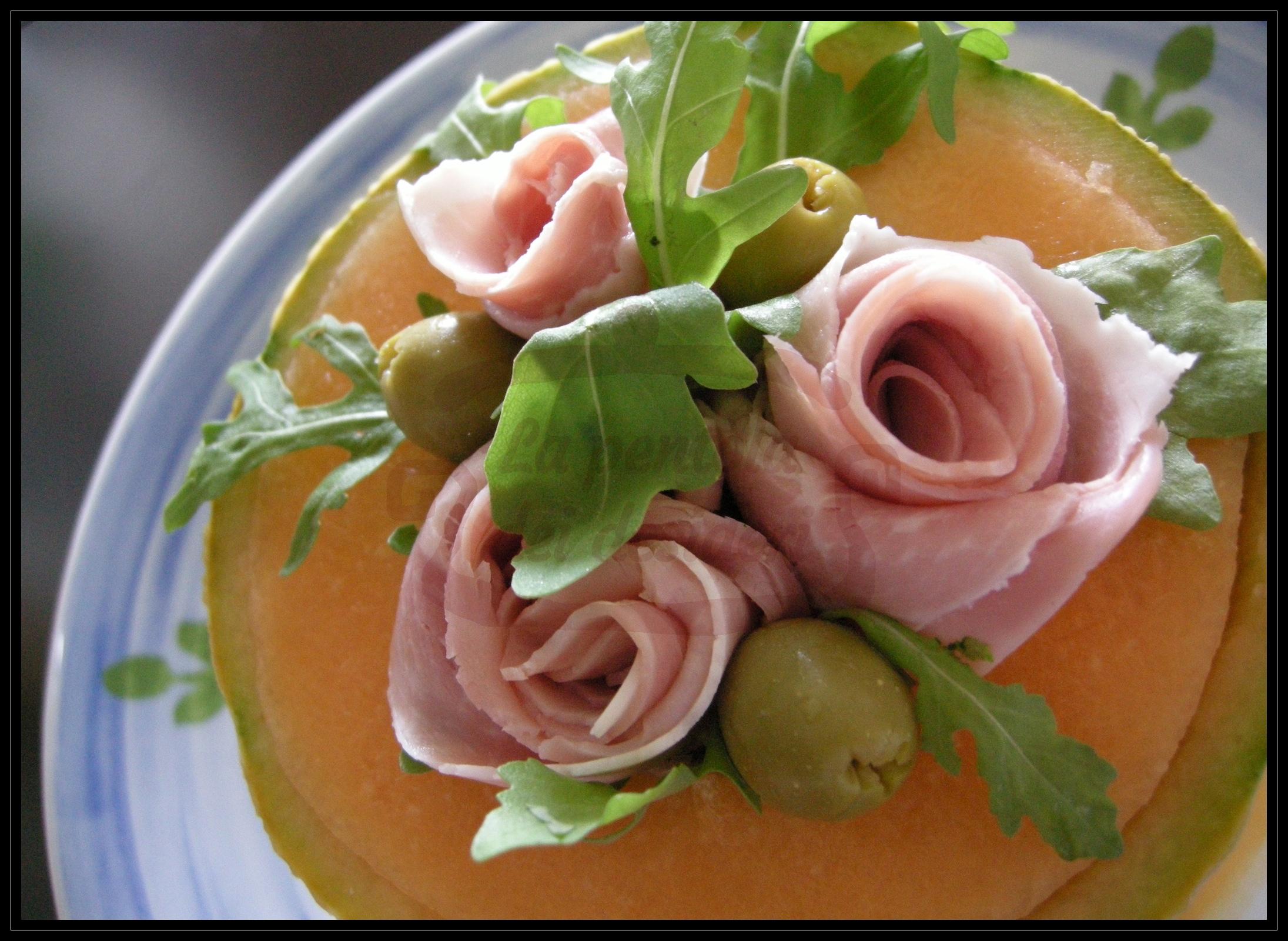 Coppa di melone con rose di prosciutto cotto, olive verdi e rucola.